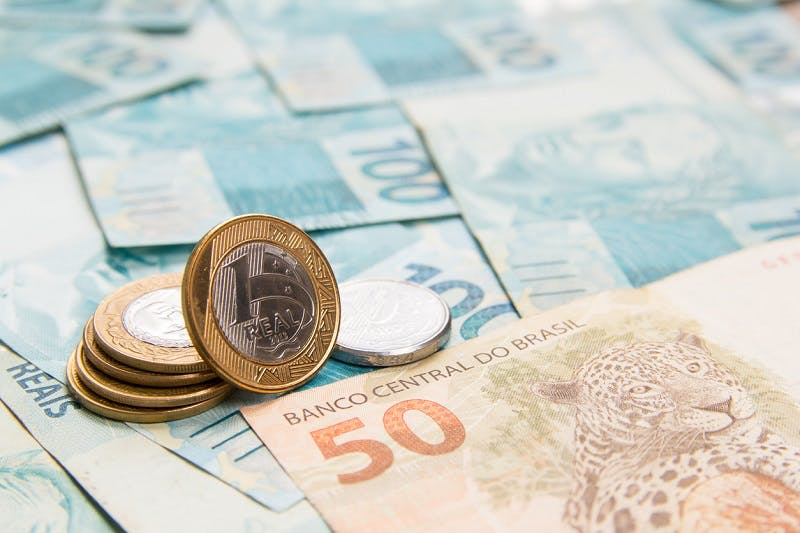 Notas e moeda de dinheiro com texto Banco Central do Brasil na nota de 50 reais