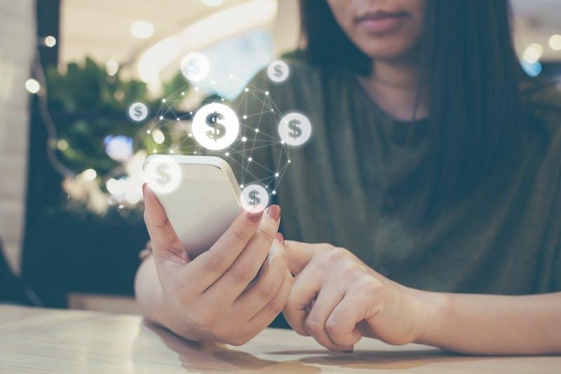 Mulher com celular na mão usando um banco digital