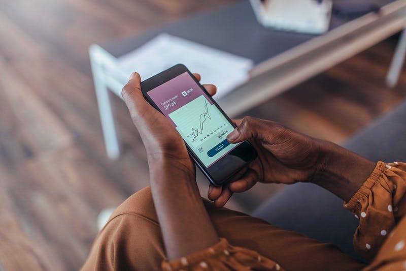 Mulher com celular nas mãos analisando seus investimentos Itaú