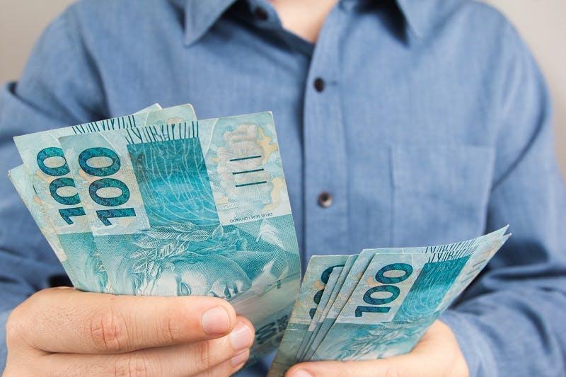 Homem com dinheiro na mão para empréstimo Itaú