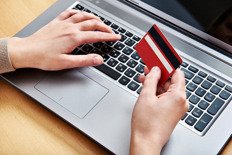 Imagem de cartão de crédito e notebook referente a Santander Cartões