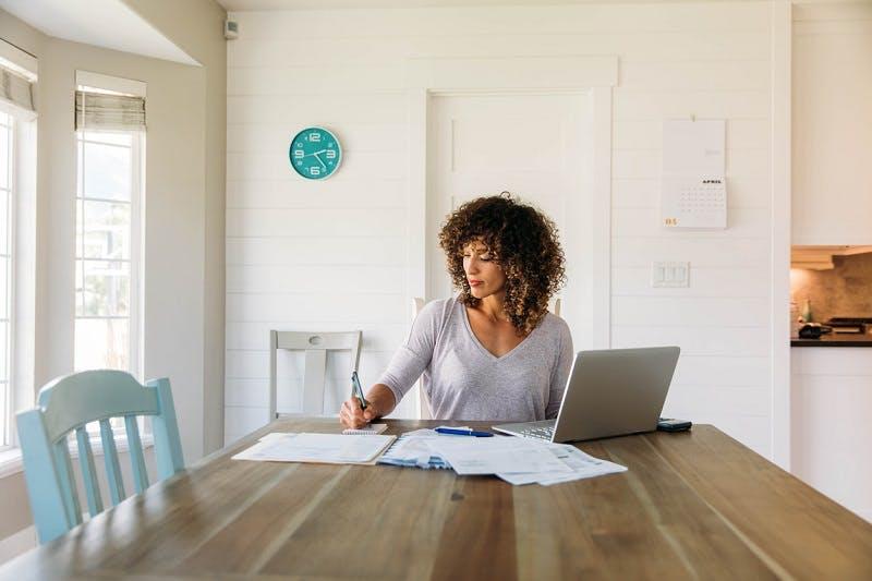 Mulher em casa fazendo contas do imposto de renda