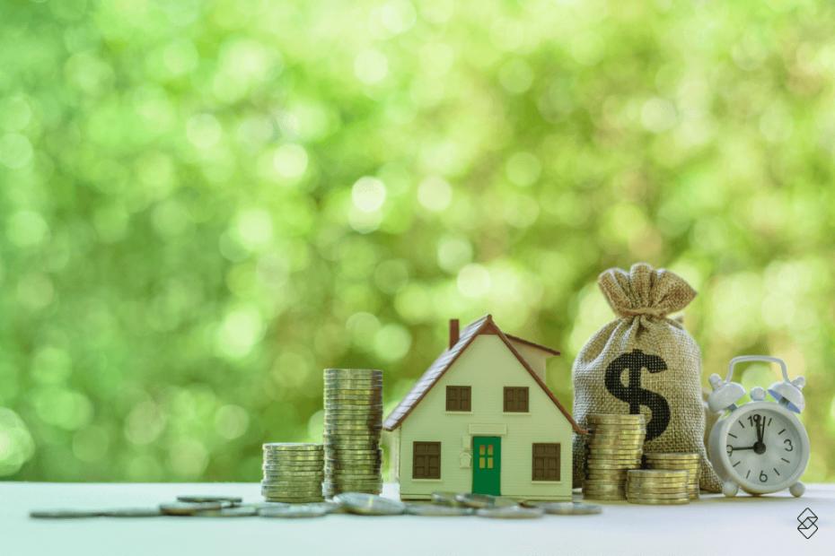 Casa e dinheiro representados em miniaturas