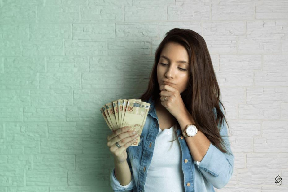 mulher com uma mão no queixo e outra segurando notas de dinheiro