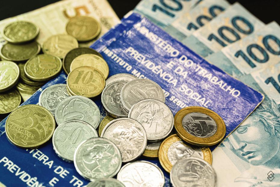 moedas sobre uma carteira de trabalho e notas de real