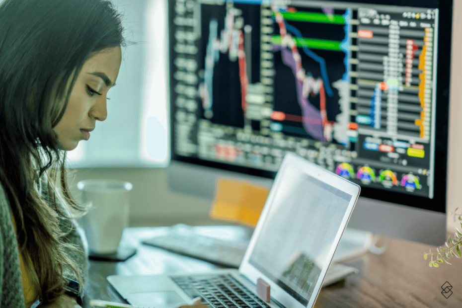 mulher sentada, mexendo em um notebook, com uma tela repleta de gráficos ao fundo