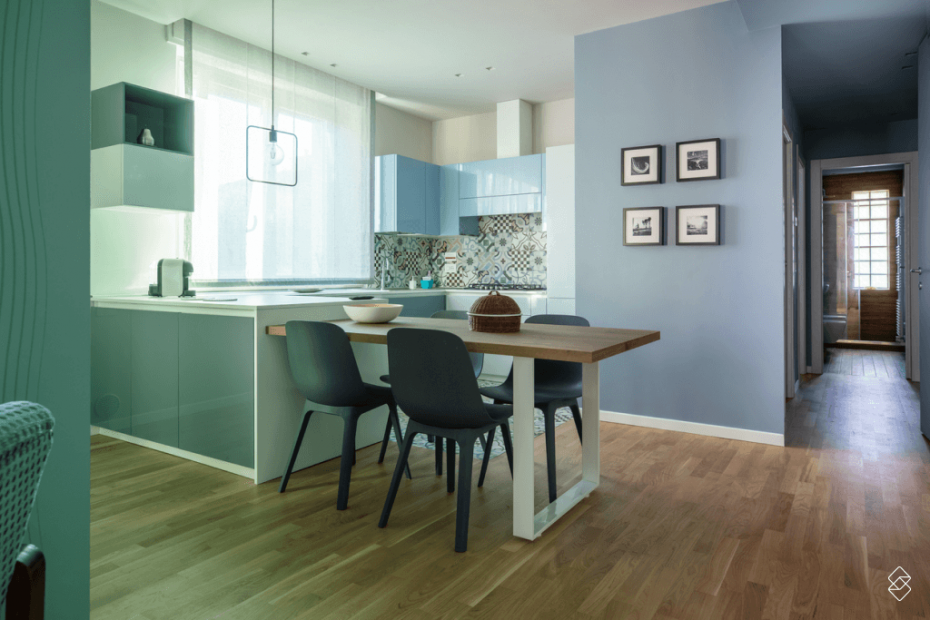 uma cozinha com mesa, cadeiras e quadros na parede