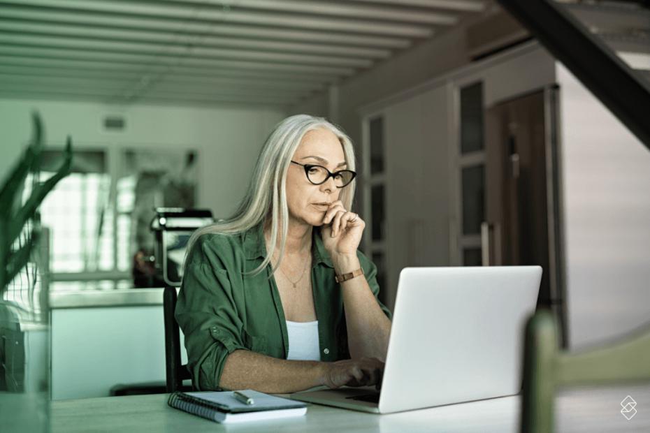 uma mulher sentada em frente a um notebook dentro de casa