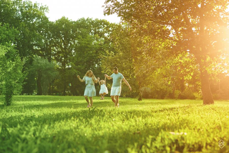 um casal levantando pelos braços uma criança em um espaço aberto, com grama e árvores