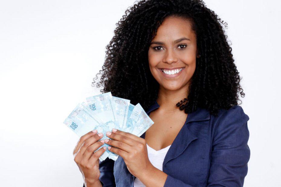 Mulher sorrindo e segurando algumas cédulas de dinheiro.