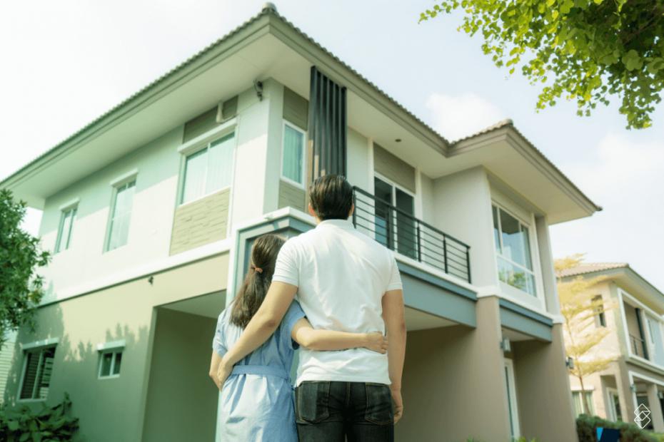um casal abraçado em frente a uma casa