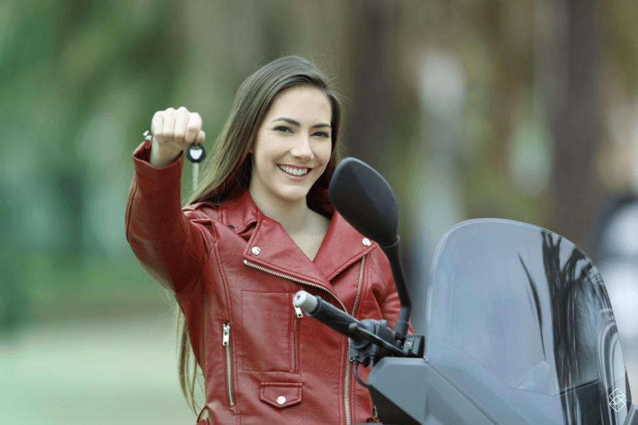 mulher em cima de uma moto segurando a chave do veículo