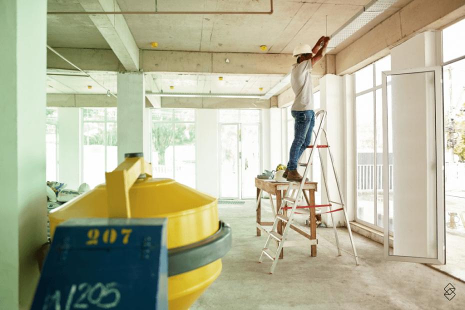 uma sala em construção, com uma betoneira e um trabalhador ao fundo