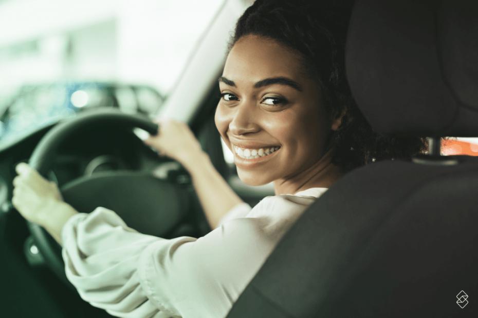 mulher segurando o volante de um carro e sorrindo