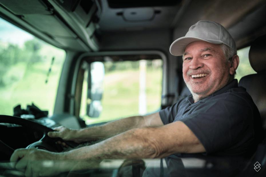 Homem de boné segurando o volante de um caminhão, representando quem pode ser contemplado com o empréstimo para autônomo