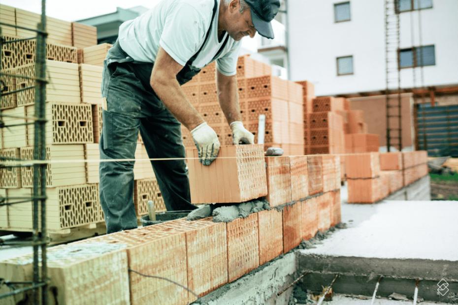 Homem com tijolo na mão construindo uma parede com dinheiro de empréstimo para construção