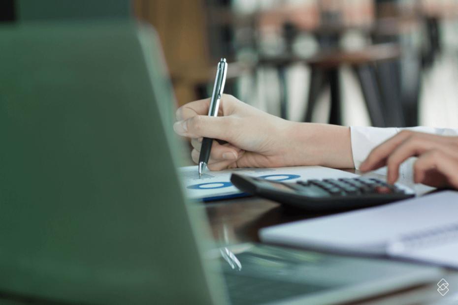 um notebook sobre uma mesa onde as mãos de uma mulher que opera uma calculadora e anota em papel