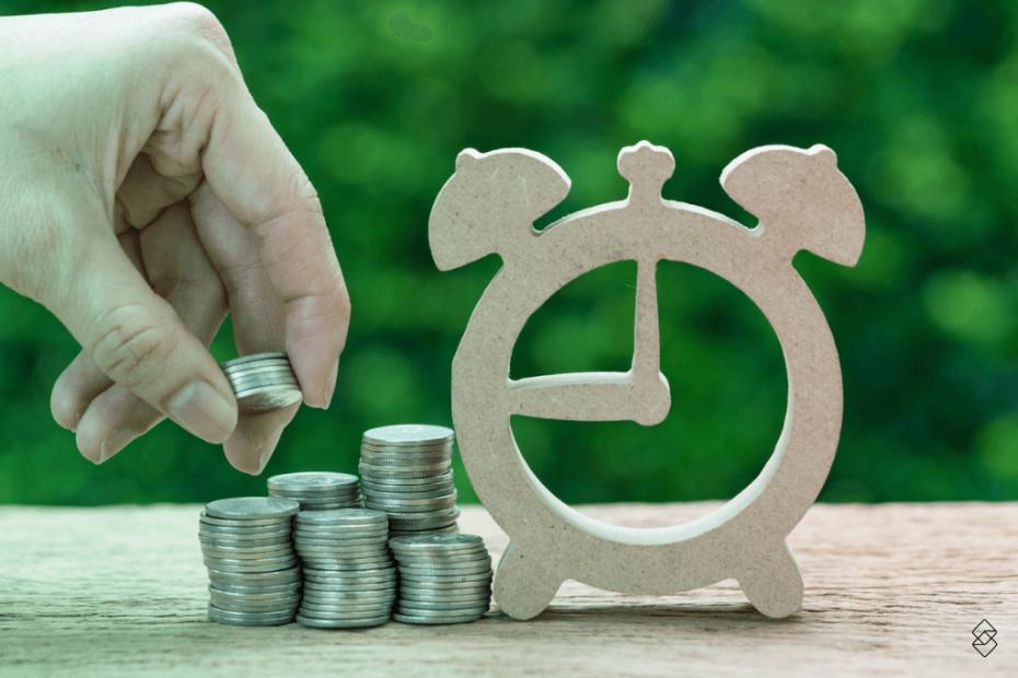 uma mão adicionando moedas a uma pilha de moedas ao lado de um relógio de papel