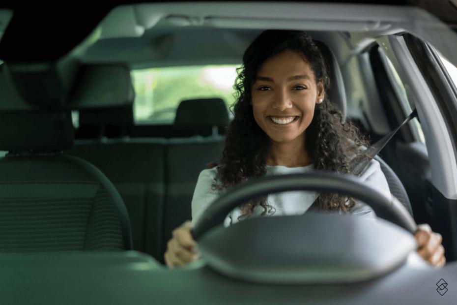 mulher segurando um volante e sorrindo por comprar um carro sem entrada