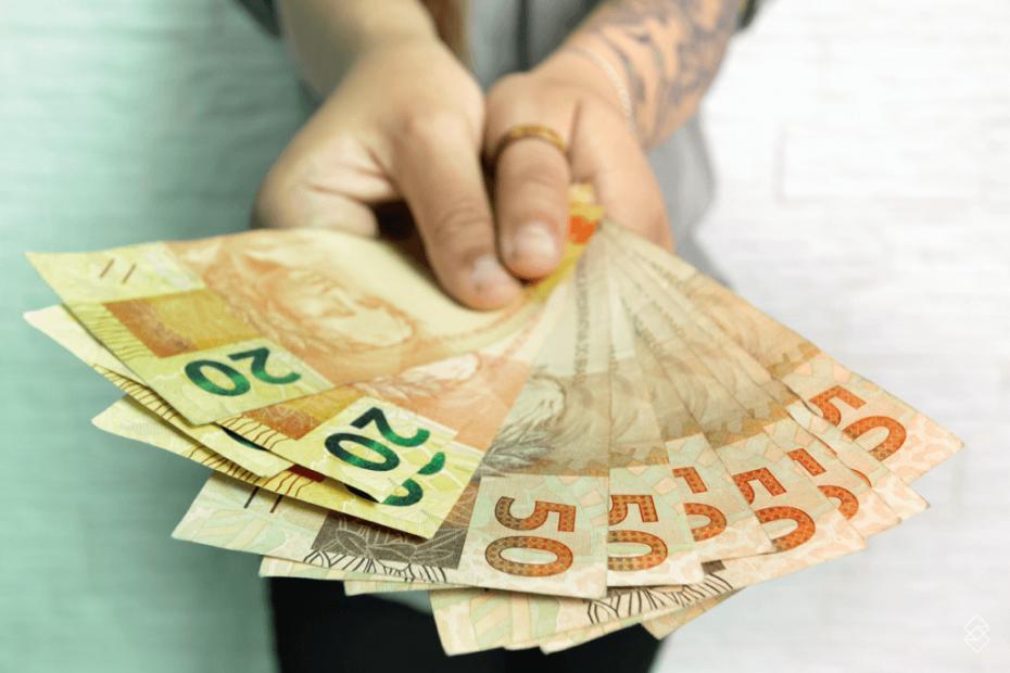 duas mãos segurando notas de R$ 50 e R$ 20
