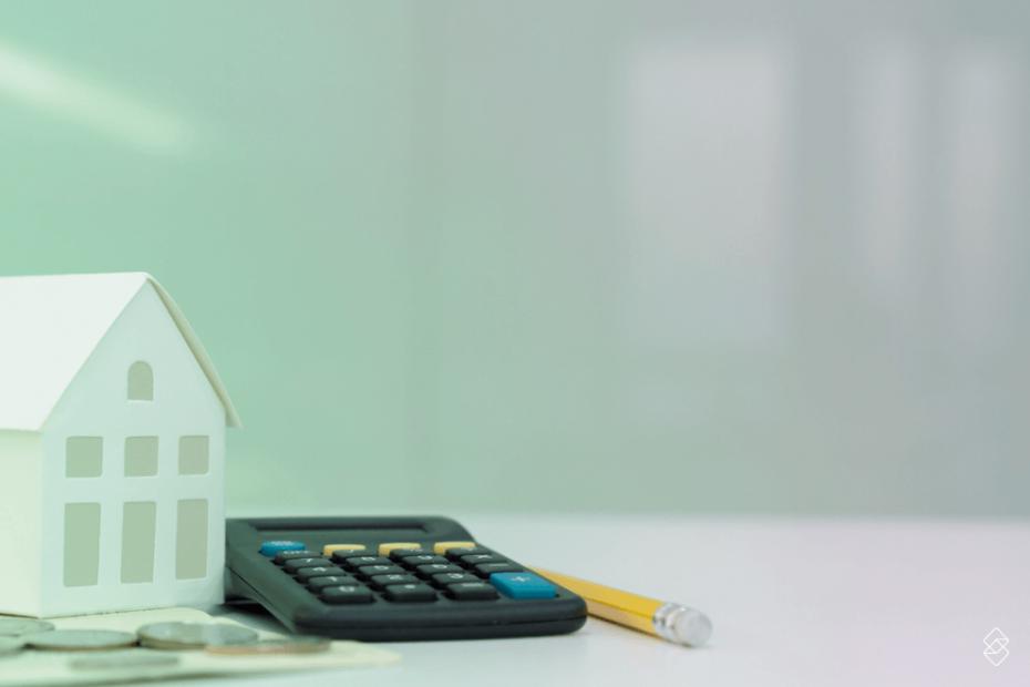 miniatura de uma casa ao lado de uma calculadora e um lápis