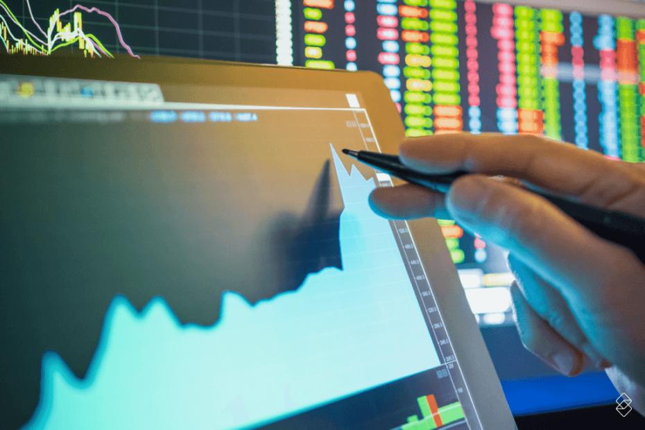 uma mão segurando uma centa e apontando para um gráfico em uma tela de computador com um painel do mercado financeiro ao fundo.