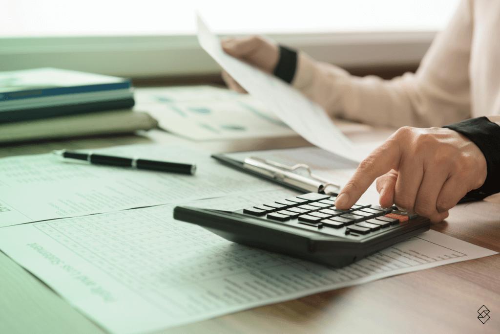 pessoa usando uma calculadora para controlar gastos