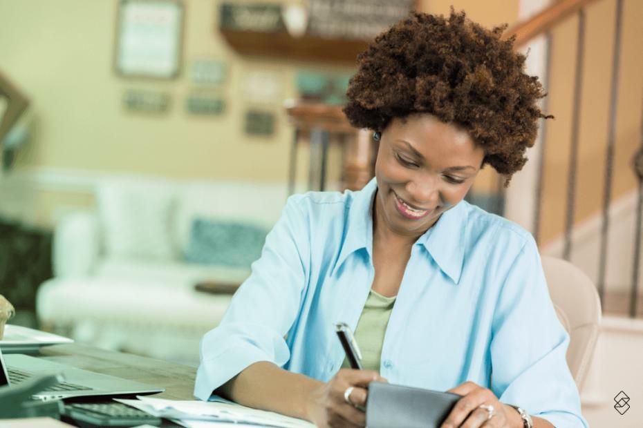 mulher sentada assinando um talao de cheque para realizar o empréstimo com cheque