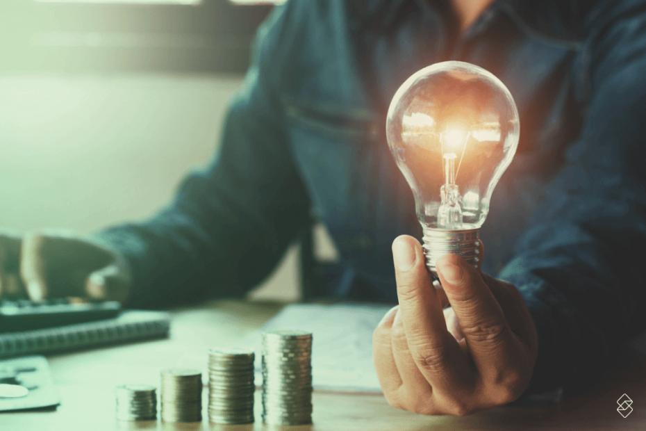 homem calculando condições do empréstimo na conta de luz e uma lâmpada acesa na sua mão esquerda