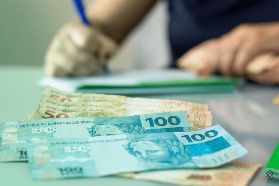 pessoa anotando em um caderno e, em frente, notas de dinheiro