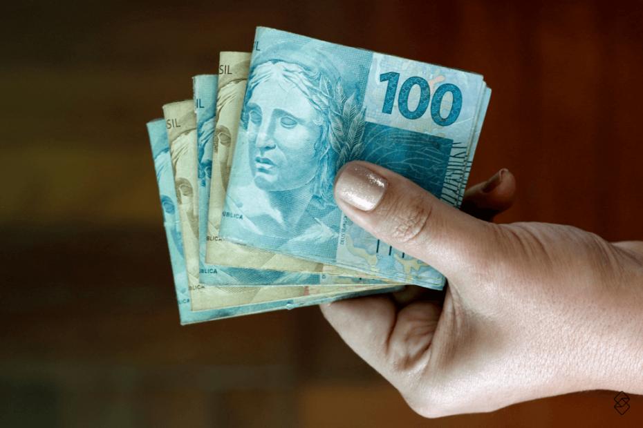mão feminina segurando notas de reais do empréstimo do saque aniversário