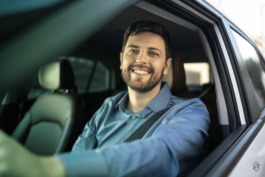 um homem dentro do carro, no banco do motorista, sorrindo