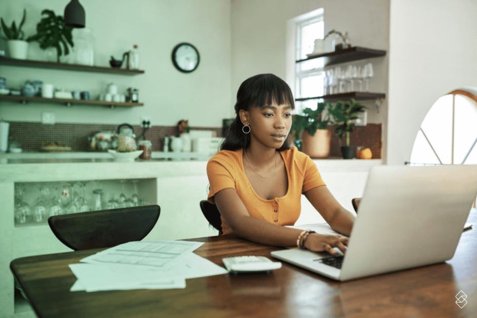 Mulher dentro de casa mexendo em um notebook fazendo sua gestão financeira pessoal