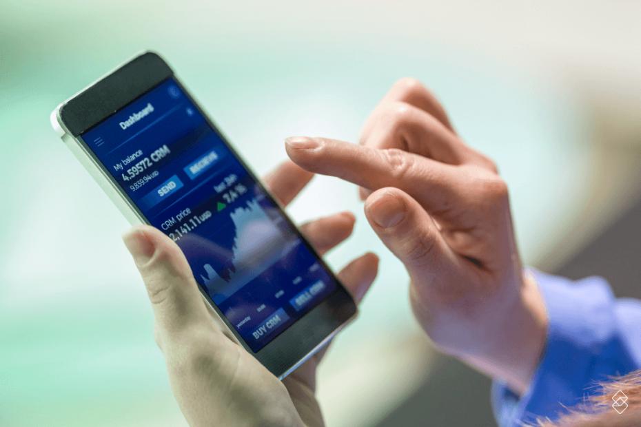 mãos de uma pessoa segurando um celular que exibe uma tela com gráficos