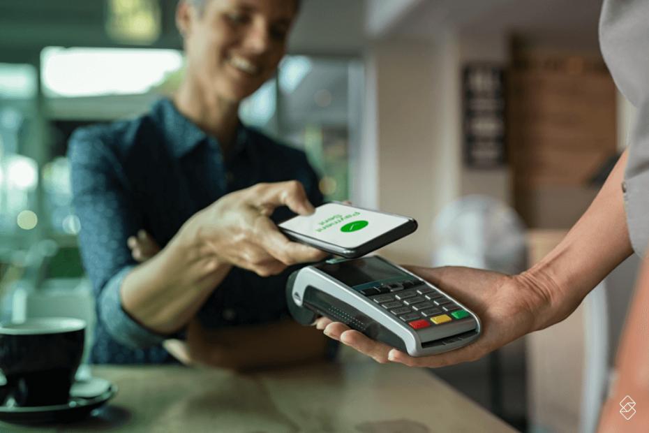 Pessoa aproximando o celular de uma máquina para efetuar um pagamento com carteira digital